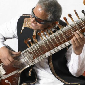 photo of Baluji Shrivastav, holding a sitar
