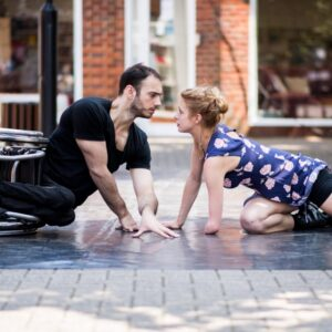Dancersm Joel Brown and Laura Patay lay on the ground facing each other, Joel's wheelchair is on its side