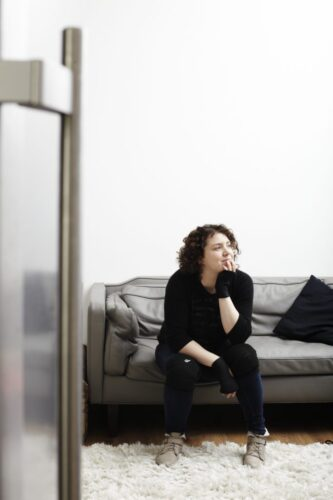 Photograph of Jess Thom sitting on a sofa.