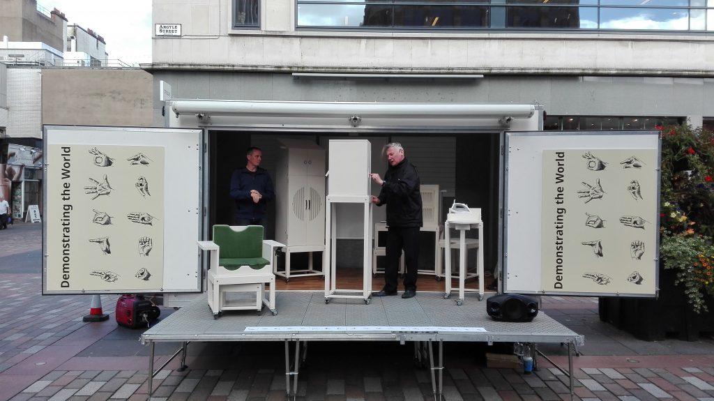 A photograph of Aairon Williamson standing on a platform surrounded by absurdist furniture. He is joined by a BSL interpreter