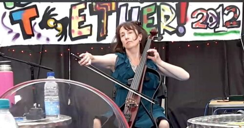 photo of performer Jo-Anne Cox playing cello with a Together 2012 banner in the background