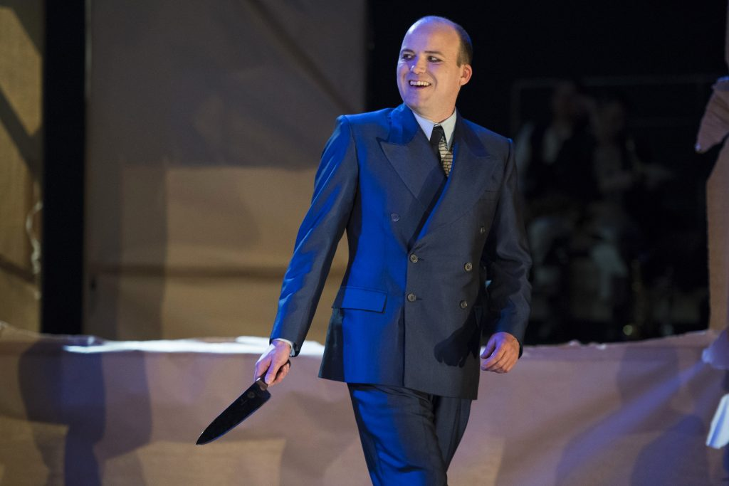 A menacing Rory Kinnear brandishes a knife with a learing expression on his face