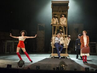 Photo of part of the movable set for the Threepenny Opera with several actors in convicts suits appearing out of a wooden tower. Debbie Kurup as Lucy Brown is prominent in the foreground, wearing red hot-pants. Stage-left stands Rosalie Craig as Polly Peachum
