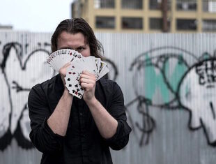 Justin stands against a wall covered in graffiti. He is holding a deck of playing cards.