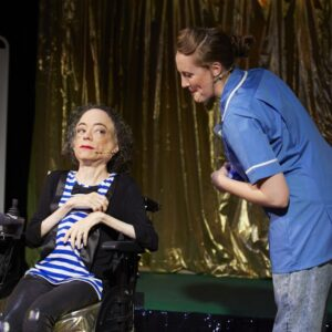 Photograph of Liz Carr performing assisted suicide the musical, a woman in a nurses outfit leans in towards her.