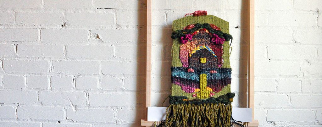 photo of multi-coloured textile work hanging against a white painted brick wall
