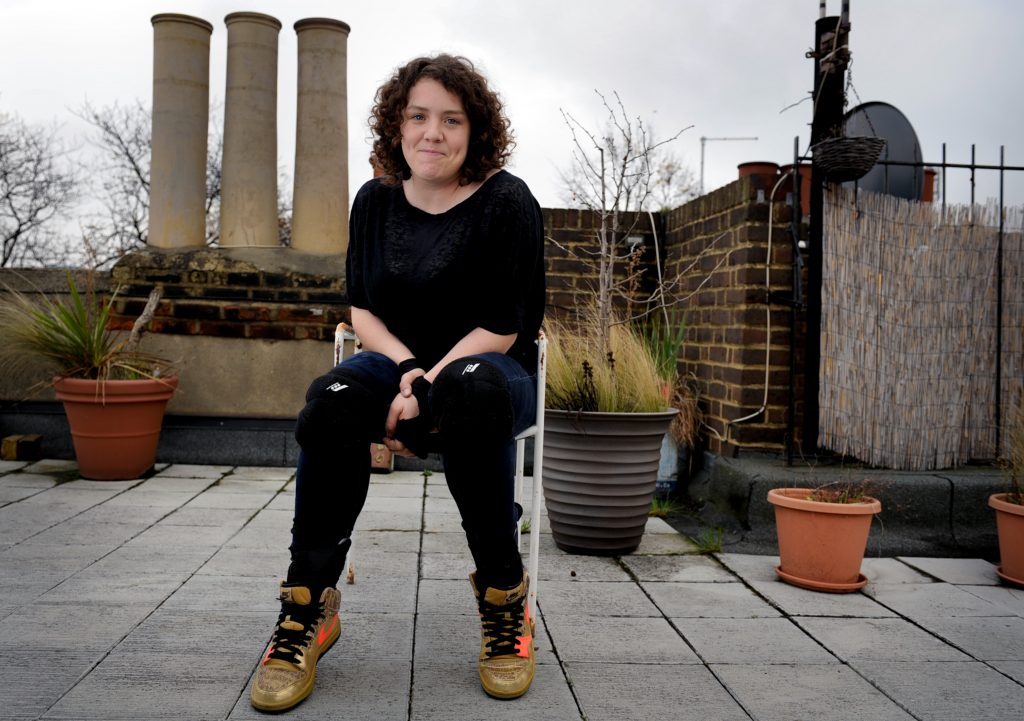 Photograph of Jess Thom sitting on a chair on a roof terrace