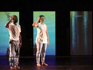 Photo of a male and a female dancer on stage in front of screens showing projections of water