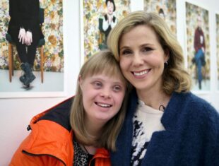 Photograph of Sally Phillips hugging Halldóra,, a woman with Down's Syndrome from Iceland.