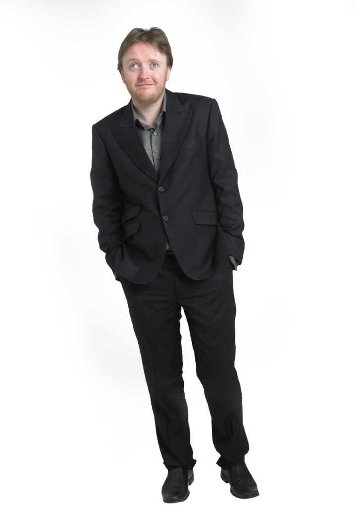 Full length shot of comedian Chris McCausland, dressed in a suit