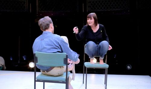 Photograph of two actors in the play Hearing Things, they are sitting on chairs facing each other, the woman is up on her tiptoes but hunched over, the man sits in a relaxed position
