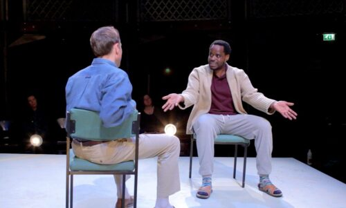 Photograph of two actors in the play Hearing Things, they are sitting on chairs facing each other.