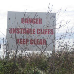 A white board with the red words Danger. Unstable Cliffs. Keep Clear