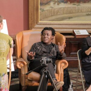 Photo of John Akomfrah sitting in an armchair as his portrait is being painted by Tanya Raabe-Webber. They are accompanied by a sign language interpreter