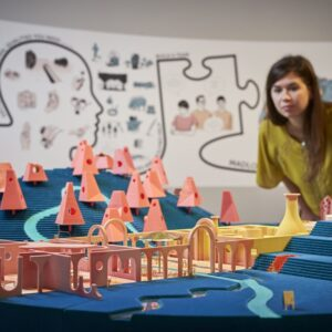 Photograph of Madlove - Designer Asylum project a woman is looking at the blue diorama with pink model buildings