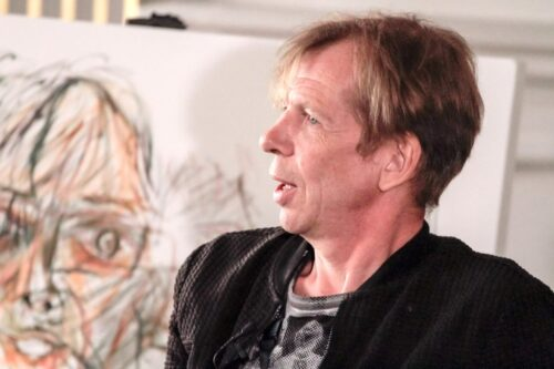 Close up of performance artist David Hoyle, without make-up in front of a canvas.