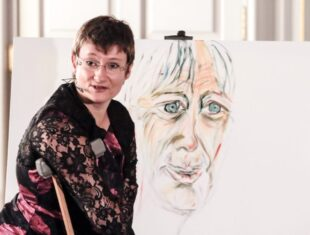Photo of artist Tanya Raabe-Webber in front of an easel.
