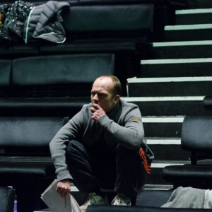 Photograph of Director Jim Pope on his haunches in the stalls of a theatre