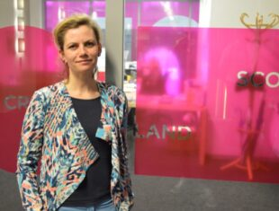 Photograph of Leonie Bell standing against a creative scotland branded window