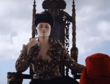 Still from a Viktoria Modesta music video, she sits on a throne with 2 red robed men attending to her