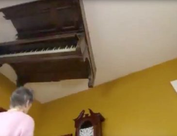Shot taken from a low camera angle of a piano on a white ceiling with an elderly white woman walking beneath