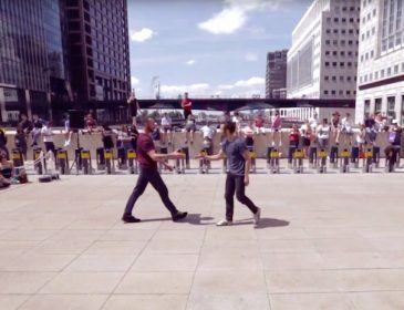 Shot of two male dancers moving towards shaking hands in an outside stage between tower blocks