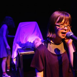 Photo of young actor with Down's Syndrome singing into a microphone