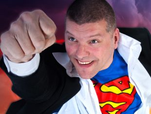 Comedian Laurence Clark dresses in a superman t-shirt and strikes the pose of the superhero