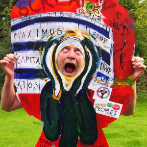 Photo of artist Vince Laws with his head through a painted panel resembling Munch's painting The Scream
