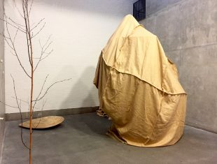 Photo of a large shape covered by brown cloth next to a tree
