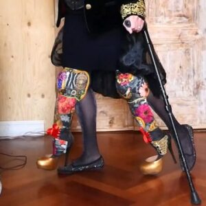 the artist wearing all black with a black crutch and elaborately decorated prosthetic legs with sparkly heels dangling from her skirt
