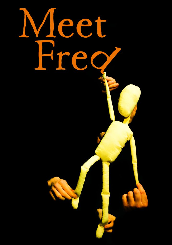 Photo of the puppet star Fred, pictured standing against a black background