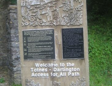 a stone with wood and metal inlays proclaiming welcocme to the Totnes - Dartington Access for All Path. One of the metal inlays is written in braille.