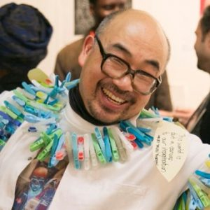 Photo of learning disabled artist Andy Kee wearing a white lab coat with coloured clothers pegs on a line around his kneck