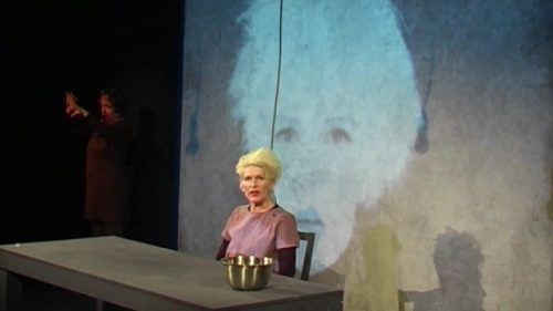 Photo of actress Jacqueline Phillips with bleach blonde hair on stage, sat next to a table - a large projection of her face behind her