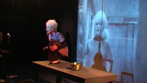 Photo of actress Jacqueline Phillips stepping out from behind a desk on stage - a large projection of her face behind her