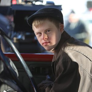 A photo of a young actor with Down's Syndrome behind the wheel of a car