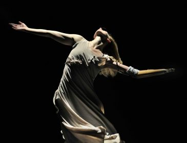Photo of female dancer in stark light against a dark background
