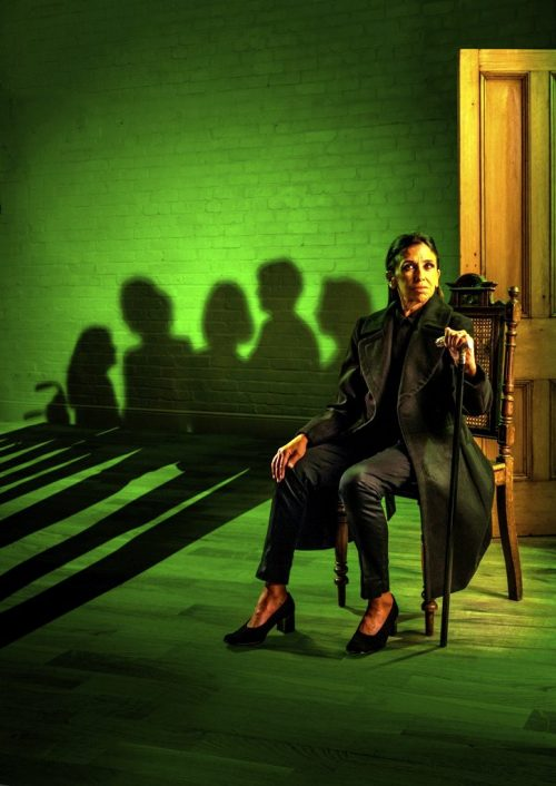 photo of actress Kathryn Hunter sitting in a change on stage under a green spotlight. Shadows of the daughters of Bernada Alba range across a brick wall at the back of the stage