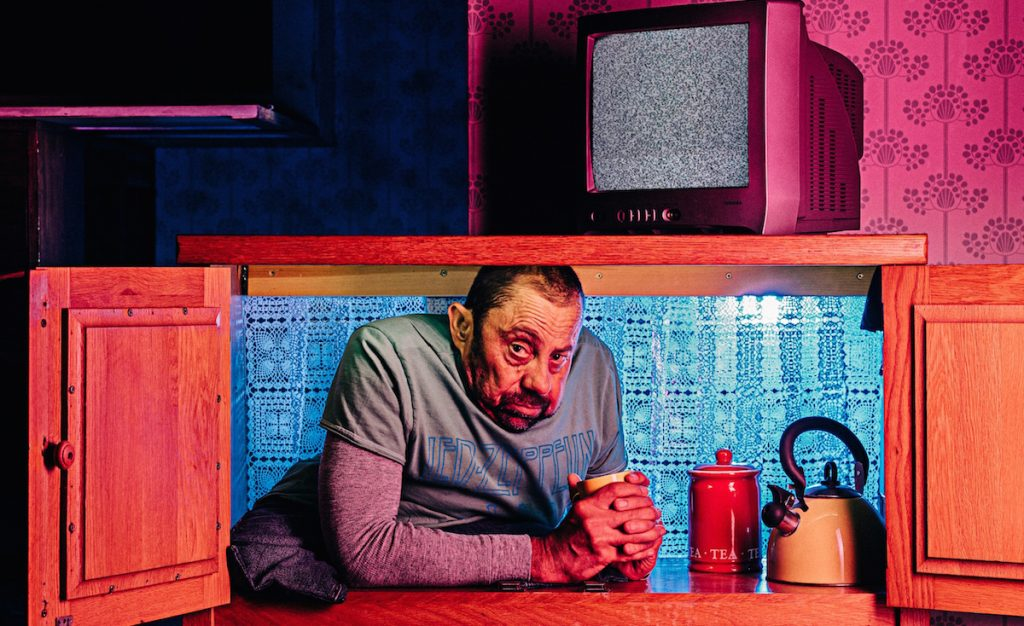 Striking image of David Toole pictured inside a cupboard with a pink tv on a shelf above his head