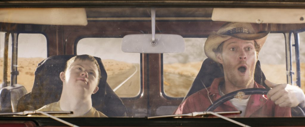 Photo of two actors with angry experesions, sitting in the front seat of a car
