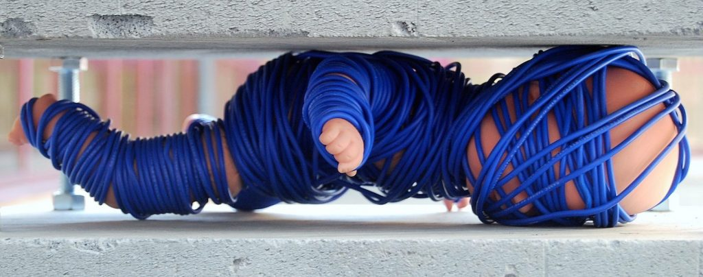 Photo of a doll bound in blue wool beneath a concrete block