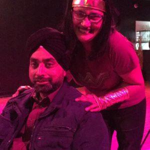 A photo of spoken word performer Kuli Kohli dressed as Wonder Woman taken through a pink filter