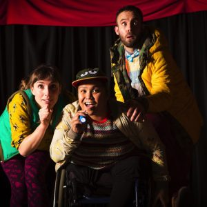 Three performers move forwards from in front of a stage curtain with tentative expressions on their faces.