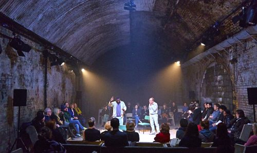 Photo of theatre production 'Hearing Things' in a large vaulted undergorund theatre space