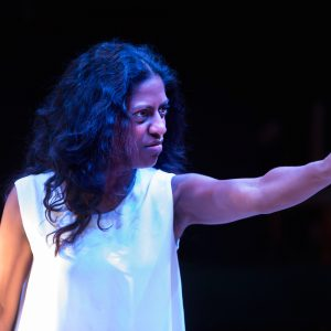 Photo of Nadia Nadarajah dressed in a white shift, looking across and pointing a dramatic finger.