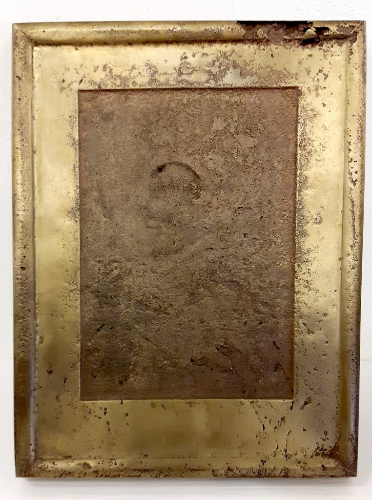 Bronze relief with a darker etched texture within a simalcrum of a portrait photograph
