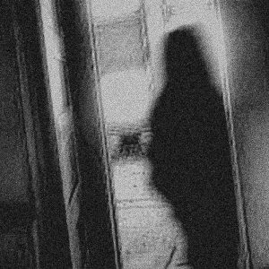 A grainy black and white image of a dark figure, perhaps a ghost