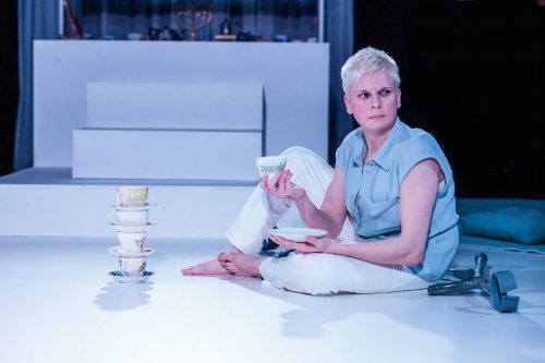 Photo of performer Claire Cunningham sitting on a floor with a stack of teacups