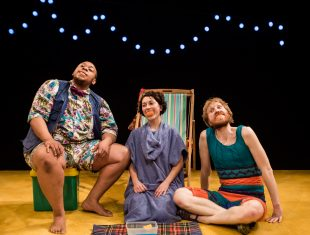 Three performers sit against a beech set